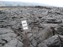 Road closed sign embedded in lava. Humorous and ironic road closed street sign, embedded in hardened lava on the Big Island of Hawaii stock photo