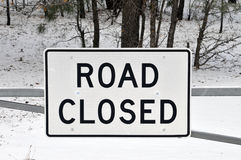 Road Closed Sign with Snowy Forst in  Background. Highway sign that indicates the snowy road behind it is closed to traffic Stock Photo