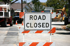 Road closed sign on street. ROAD CLOSED sign on a street with construction equipment in the background royalty free stock images