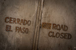 Road closed. In Spanish and English. Painted on an old metal door Royalty Free Stock Photo