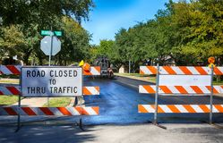 Road closed to thru traffic sign. Green and quiet neighborhood street closed for maintenance stock photography