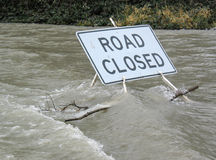 Road Closed By Water. A Road Closed sign stands in flood waters from a nearby river, Washington State Stock Photo