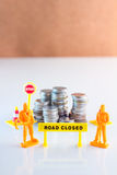 Road closed for your money. Money crisis coins tower with workmen and signage financial concept Royalty Free Stock Image