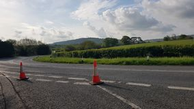 Road closure with traffic cones. Road closure traffic cones nobody sussex uk highway junction shut diversion safety clouds corner repair markings sunny closed royalty free stock photos