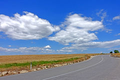 The road in the clouds in Traquinia. An asphalt road runs between the blue sky and the clouds in the territory of Tarquinia Viterbo Italy royalty free stock photos
