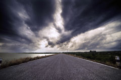 On the road. Cloudy sky oover the road Royalty Free Stock Images