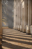 Road with columns details. Architectural element with selective focus. Columns in shadows on sunny daylight. Road and architecture fragment. Architecture Stock Image