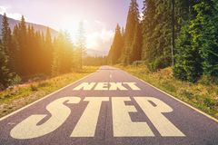Road concept, Next Step written on the road in the mountains.  Stock Photos