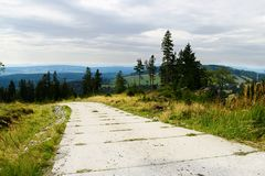Road with concrete slabs pavement on hill in the Owl Mountains Landscape Park, Sudetes, Poland. Stock Images