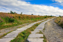 Road of concrete slabs uphill to the sky. Road of concrete slabs through the field turns uphill to the sky stock image