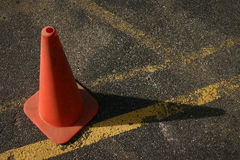 Road Cone on Pavement. Orange road construction cone on pavement with yellow parking lines. Horizontal format. Area to right for title graphic Stock Photos