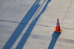 Road Cone at Sunset With Angled Shadows. A road cone on the sidewalk Stock Images