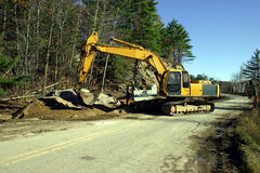 Road Construction. A man is operating an hydraulic drill boring a hole into rocks so that it can be blasted with explosive afterwards while and excavator is Stock Photo