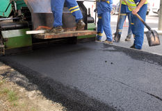 Road in construction. Some workers building a road working with hot asphalt Stock Photos
