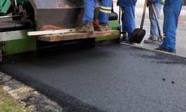 Road in construction. Some workers building a road working with hot asphalt Royalty Free Stock Photo