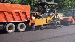 Road construction. Applying new hot asphalt. Royalty Free Stock Photos