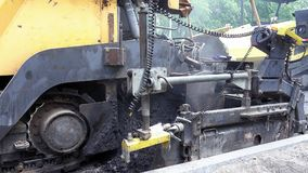Road construction. Applying new hot asphalt. Road construction. Applying new hot asphalt using road construction machinery and power industrial tools. Roadworks Stock Photos