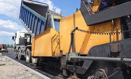 Road construction. Applying new hot asphalt. Road construction. Applying new hot asphalt using road construction machinery and power industrial tools. Roadworks Royalty Free Stock Photography