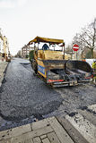 Road Construction on a city street renewal. BRUSSELS, BELGIUM - NOVEMBER 29, 2014:  An asphalt spreader is used to place layer of asphalt and steam roller Stock Image