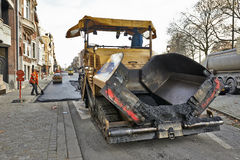 Road Construction on a city street renewal. BRUSSELS, BELGIUM - NOVEMBER 29, 2014:  An asphalt spreader is used to place layer of asphalt and steam roller Royalty Free Stock Image