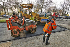 Road Construction on a city street renewal. BRUSSELS, BELGIUM - NOVEMBER 29, 2014:  An asphalt spreader is used to place layer of asphalt and steam roller Royalty Free Stock Photo