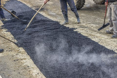 Road construction crew used shovels to scatter more asphalt 2 Stock Photos