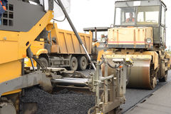 Road construction equipment. Industrial pavement truck or machine laying fresh bitumen and asphalt on base of a highway construction Stock Image