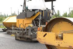 Road construction equipment. Industrial pavement truck or machine laying fresh bitumen and asphalt on base of a highway construction Royalty Free Stock Photography