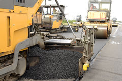 Road construction equipment. Pavement machine laying fresh asphalt or bitumen on top of the Royalty Free Stock Photo