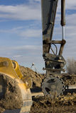 Road construction - excavator arm with roller. Road construction - excavator arm with a roller to compact the fill over newly placed sewer pipe, backhoe scoop Stock Images