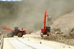 Red excavator operating at mountain royalty free stock photo
