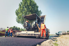Road construction. Men and heavy machinery at work Royalty Free Stock Photos