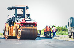 Road construction. Men and heavy machinery at work Royalty Free Stock Photography