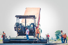 Road construction. Men and heavy machinery at work Stock Photography