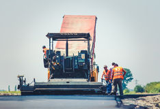 Road construction. Men and heavy machinery at work Stock Photo
