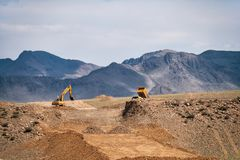 Road construction in Mongolia. Excavators and dump truck performs earthworks. KHOVD, MONGOLIA - JULY 06, 2017: Road construction in Mongolia. Excavators and dump stock photography