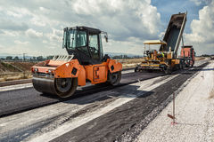 Road Construction. Pavement machine laying fresh asphalt or bitumen on top of the gravel base during highway construction Stock Photography