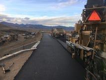 Road construction paving machine with truck delivering asphalt stock images