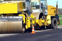 Road construction in progress, asphalting road with modern equipment. Road construction in progress, asphalting with modern equipment Royalty Free Stock Photo