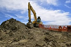 Road construction site with excavating machine. Excavating machine moving earth at a road construction site royalty free stock image
