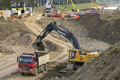 Road construction with truck and excavator. Netherlands, Gelderlland province: Roadworks near the village Heumen. An excavator loads a truck with earth Stock Photos
