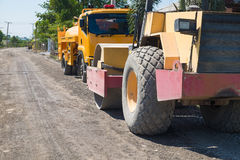 Road construction vehicle on the rough rural road. Royalty Free Stock Images