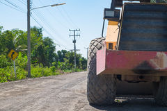 Road construction vehicle on the rough rural road. Royalty Free Stock Image