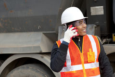 Road construction worker. Using mobile phone standing in beside truck Stock Photography