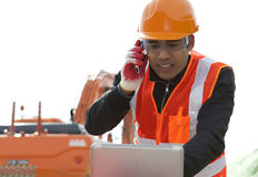 Road construction worker. Talking on mobile phone and using laptop computer standing front excavator Stock Image