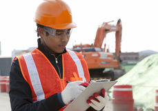 Road construction worker. Checking a document on the excavator background Stock Images