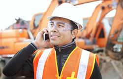 Road construction worker in front of excavator. Road construction worker using mobilephone standing in front of excavator Stock Photography