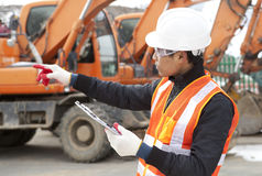 Road construction worker in front of excavator. Road construction worker and heavy equipment on the background Royalty Free Stock Image