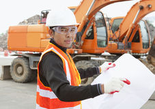 Road construction worker in front of excavator. Road construction worker and heavy equipment on the background Royalty Free Stock Images