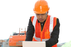 Road construction worker with  laptop. Road construction worker using laptop standing front excavator Royalty Free Stock Photo